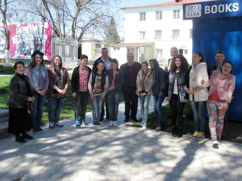Jugendliche stehen im Herbst vor einem Buchladen