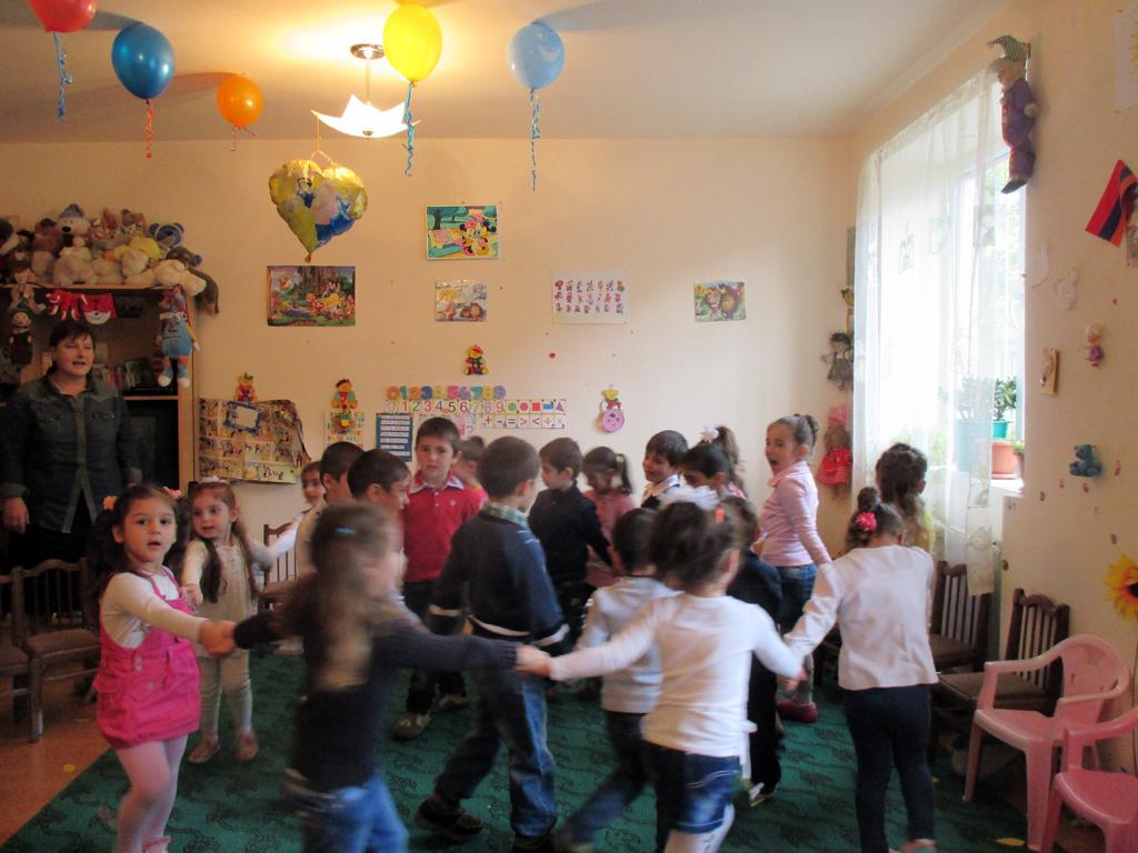 Viele Kinder tanzen im Kreis im geschmückten Kindergartenraum in Alaverdi