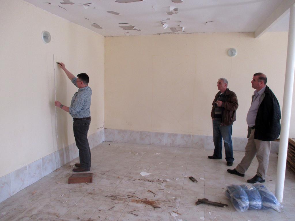 Anzeichnen von Maßen an den Wänden des sanierungsbedürftigen Gebäudes