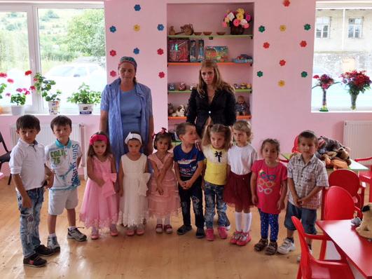 Kinder mit ihren Betreuerinnen im neuen, rosa gestrichenen Spielzimmer in Koreti.