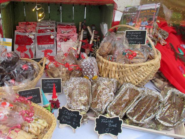 """Auslage des Weihnachtsmerktstands mit Stollen, Früchtebrot, Spekulatius und mit dem Flyer """"Care for Kids"""""""
