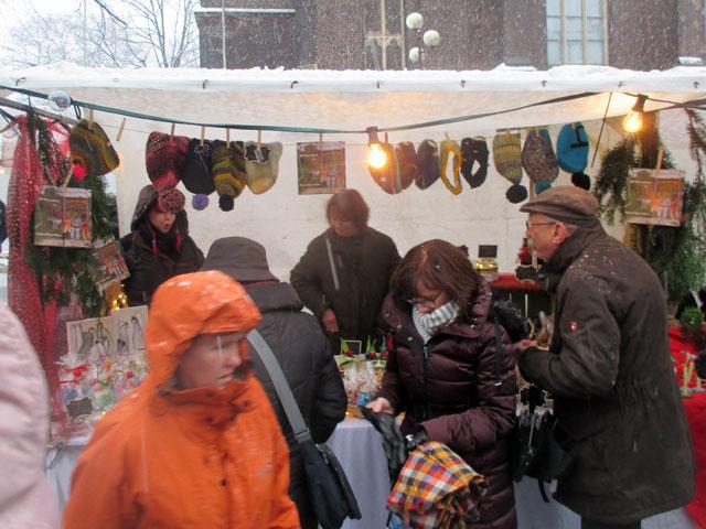 Der Weihnachtsmarktstand im Schneetreiben und dichtem Gedränge