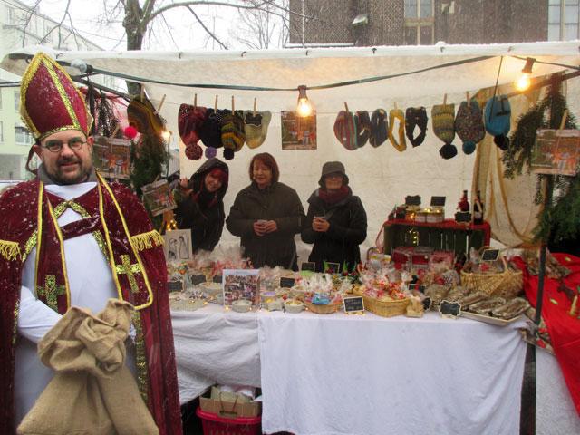 Der Weihnachtsmarktstand mit dem Standpersonal und dem Nikolaus